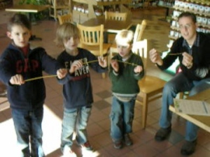 Kids breaking spaghetti during our free science experiment Second Saturday Science